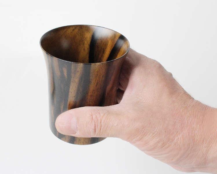 お酒を嗜む際の器は様々な材質のものがありますが、温かみを感じる木製の器がお好きな方も多いことでしょう。一般的によく見かけるのは、ケヤキ、ヒノキ、サクラ…などの木材で作られたものだと思いますが、非常に珍しい「柿の木」で作られた酒器があるのはご存知でしょうか?