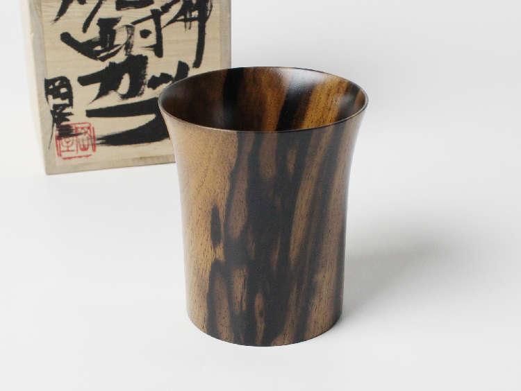 島根県出雲地方に伝わる伝統的な技法を基礎に、日々の暮らしを彩るインテリアと木工芸品を製作している「おかや木芸」では、希少で、且つ神秘の文様を持つことから天からの恵みとも言われている「出雲黒柿」で珍しい焼酎カップを製作しています。「黒柿焼酎カップ」