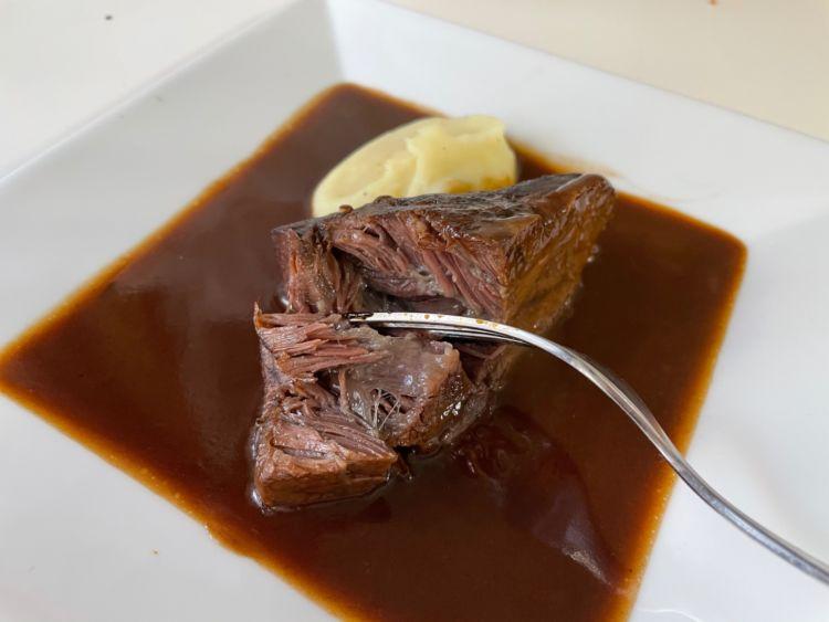 フォークで刺された和牛ほほ肉の赤ワイン煮込み
