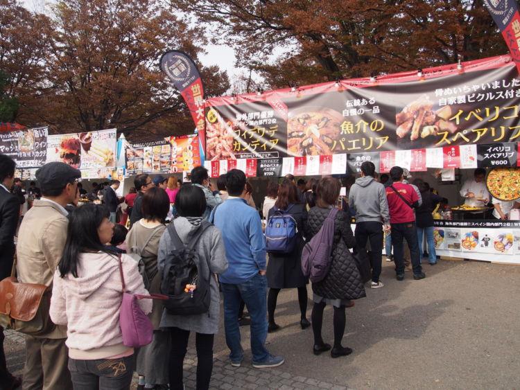 「フィエスタ・デ・エスパーニャ2018」の開催会場は、東京の代々木公園。大規模イベント開催場所の メッカとして知られています。 「フィエスタ・デ・エスパーニャ2018」のイベントの開催は午前10時から。オープンを待ち望んでいた多くの方々が、スタートと同時にお目当てのブースに並びはじめました。そして1時間もしないうちに会場のテーブル席は来場者でいっぱいになりました。 飲食関係のブースは、約30店舗。開場にあわせてすぐに提供できるよう早めに調理をしていたところが多く、そこかしこから美味しそうな香りがしてきます。